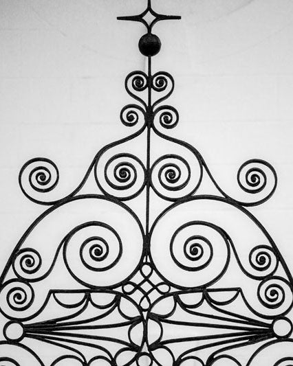 Black and white photograph of beautifully decorative ironwork in Charleston, South Carolina, a city known for a long history of fine ironwork in its architecture and fences.