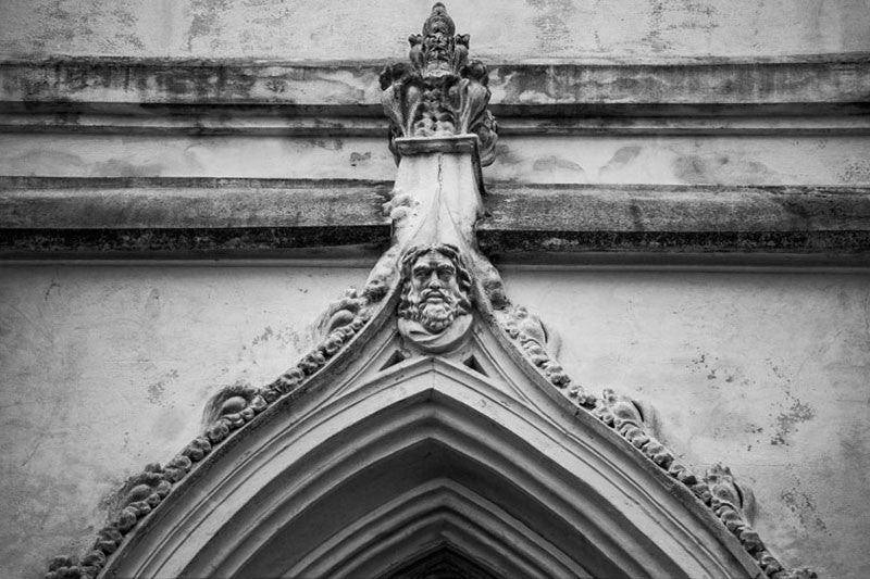Black and white architectural detail photograph of a face carved atop the apex of a pointed arch in Charleston, South Carolina.