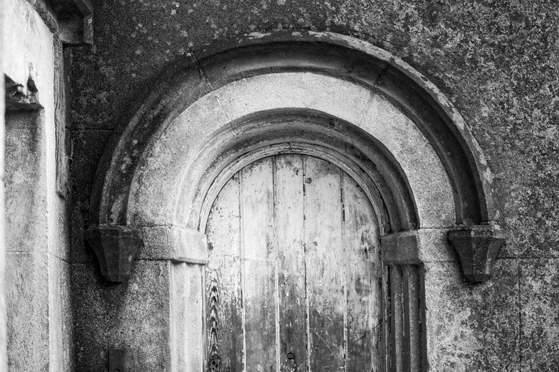 Black and white photograph of an old wooden door set under an arch, flanking the main front entrance to the old Charleston County Jail, which was built in 1802.