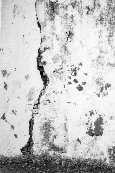Black and white architectural detail photograph of a crack on the white-washed exterior wall at the old Charleston Jail, which was built in 1802 and remained in service until 1939.