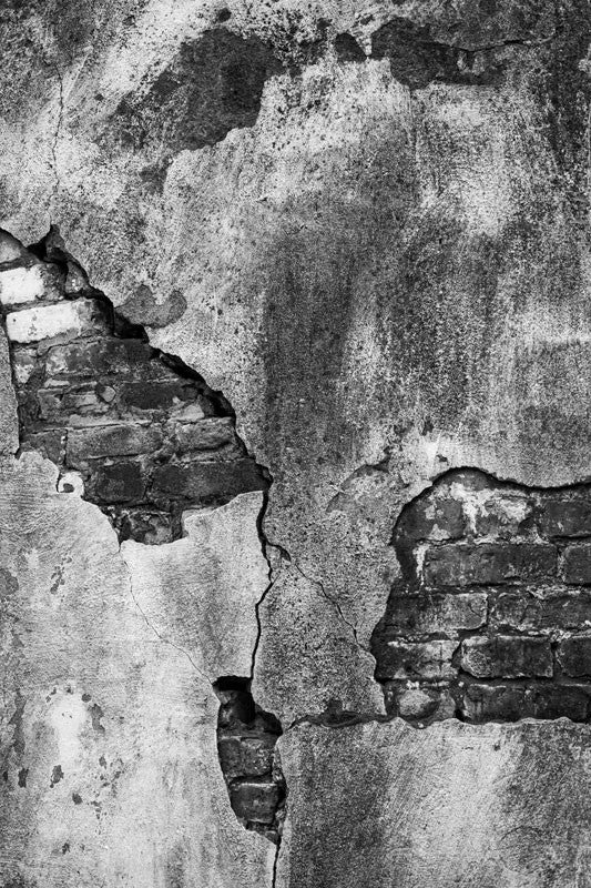 Black and white architectural detail photograph of a bricks peeking through the cracked cement of an exterior wall at the old Charleston Jail, which was served from 1802 until 1939.