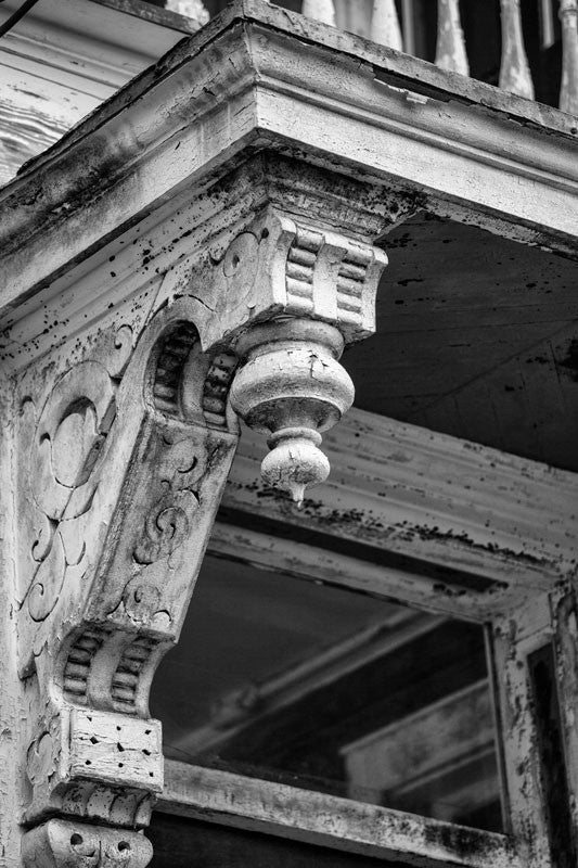 Black and white photograph of an architectural detail on a neglected but beautiful Victorian house in Charleston, South Carolina.