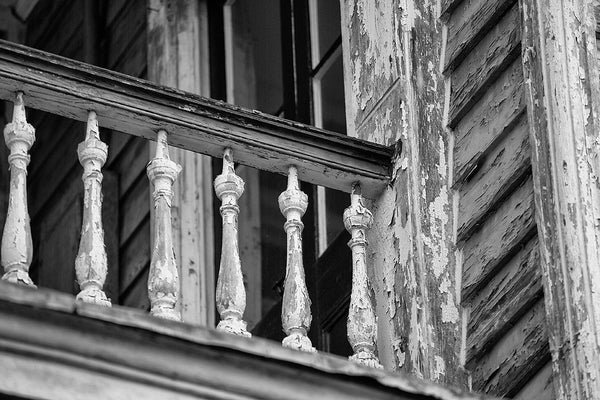 Black and white architectural detail photograph of antique wooden handrail on the second story porch an old house in Charleston, South Carolina.