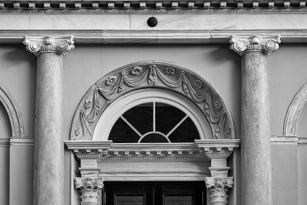 Black and white architectural detail photograph of decorative designs over the doors to the historic Charleston City Hall. Designed by local architect Gabriel Manigault in the Adamesque style, the structure was opened in 1804 to be a branch of the federal bank, but was transferred to the city in 1811 after revocation of the bank's charter by the U.S. Congress.