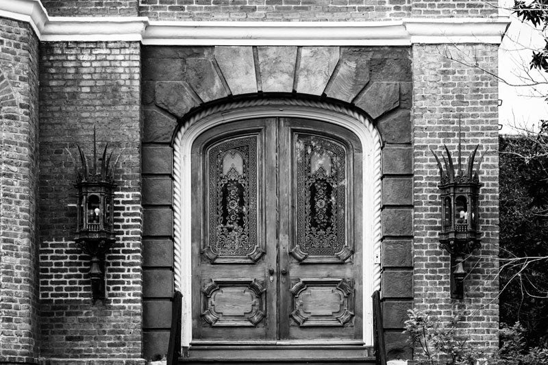 Black and white architectural photograph of fancy glass and wood doors of a large, historic mansion, near the battery on Meeting Street in Charleston, South Carolina.