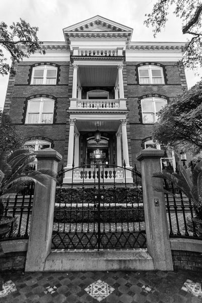 Black and white photograph of Charleston's Calhoun Mansion, as seen looking up from the sidewalk outside the entry gate.