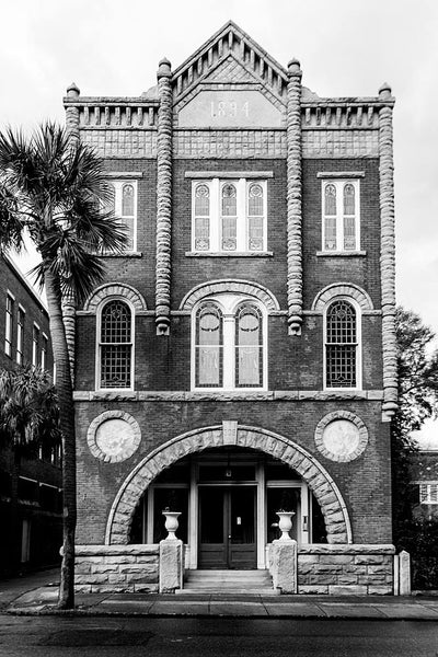 Black and white photograph of a unique historic building at 309 Meeting Street in Charleston. As the front of the building testifies, this beautiful structure was built in 1894 and served originally as the Connelley Funeral Home.
