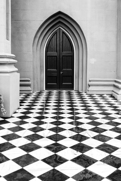 Black and white photograph of a historic churchyard in Charleston that features striking fence-to-fence checkerboard tiles.