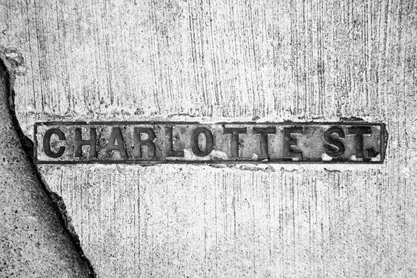 Black and white photograph of a Charlotte Street sidewalk sign in historic Charleston, South Carolina.