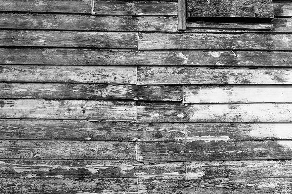 Black and white photograph of textured and weathered wood on the side of an old house in Charleston, South Carolina.