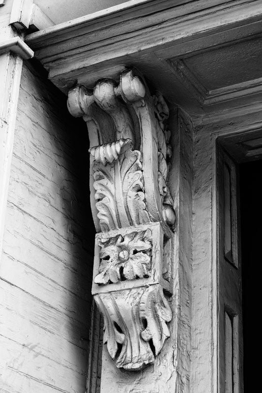 Black and white photograph of an architectural detail -- heavily painted and somewhat dusty ornate woodwork on an old house in Charleston, South Carolina.