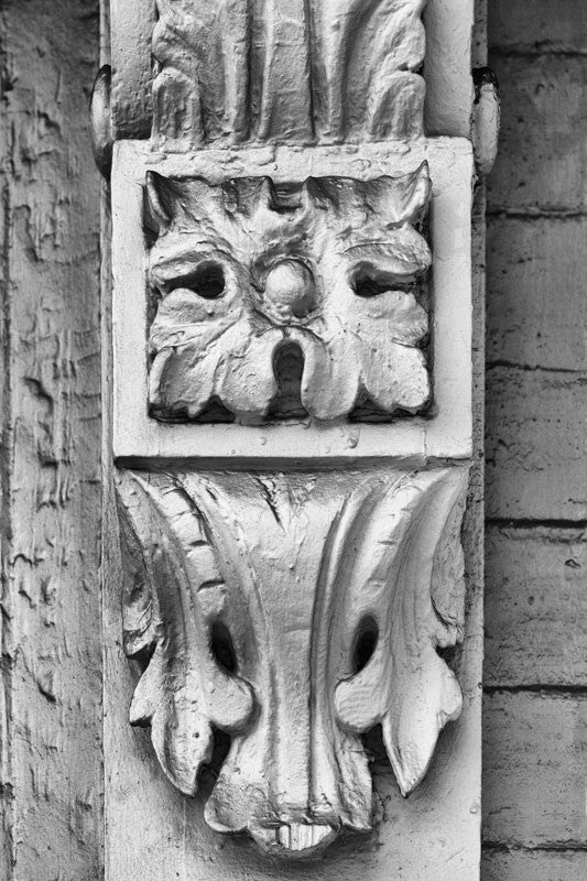Black and white close-up detail photograph of antique woodwork on an old house in Charleston, South Carolina.