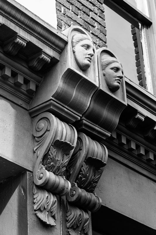 Black and white architectural detail photograph of female faces in the decorative scrollwork on buildings dating to the 1890s on Charleston's Meeting Street.