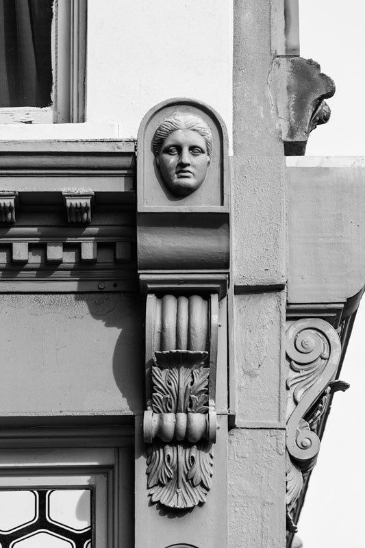 Black and white architectural detail photograph of a female face in the ornamental scrollwork on an 1890s-era building on Charleston's Meeting Street.