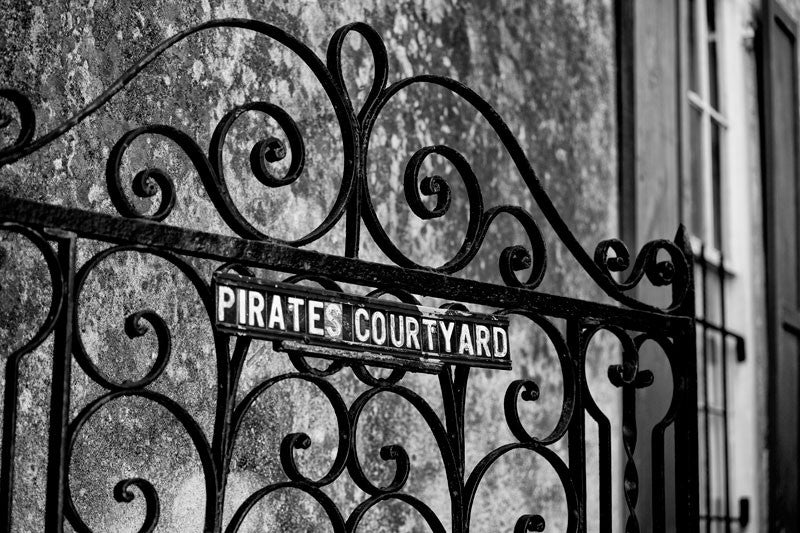Black and white photograph of an ornamental iron work gate for the Pirate's Courtyard in the French Quarter area of Charleston, South Carolina.