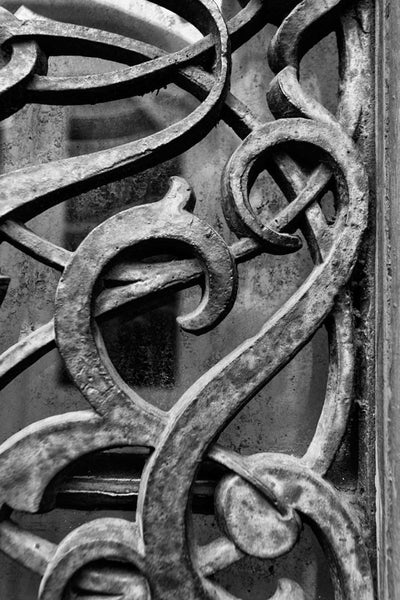 Black and white detail photograph of the ornate antique iron work on the exterior doors and windows of the old Farmers and Exchange Bank, built circa 1853.