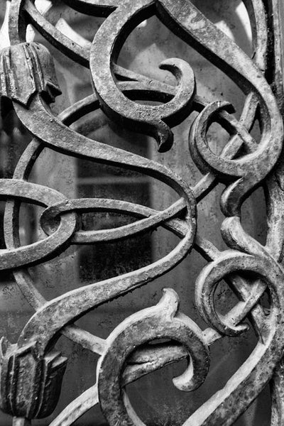Black and white photograph of the iron work over the exterior door and window glass at the old Farmers and Exchange Bank, built in 1853.