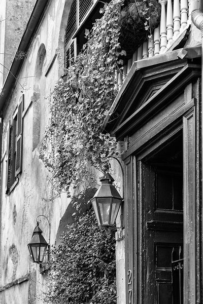 Black and white architectural photograph of a romantically beautiful old building on State Street in Charleston, with working gas lamps and ivy flowing from the second floor balcony.