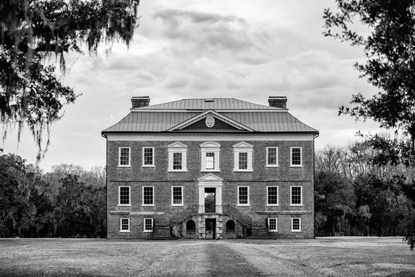 Black and white photograph of the front exterior of Drayton Hall, nine miles outside Charleston. Drayton Hall was built about 1740, and is the only South Carolina plantation home to survive the Revolutionary War and the Civil War intact. The house is now held in a state of preservation, maintained but not restored, which means that original paint, woodwork, and carved ceilings can still be seen.