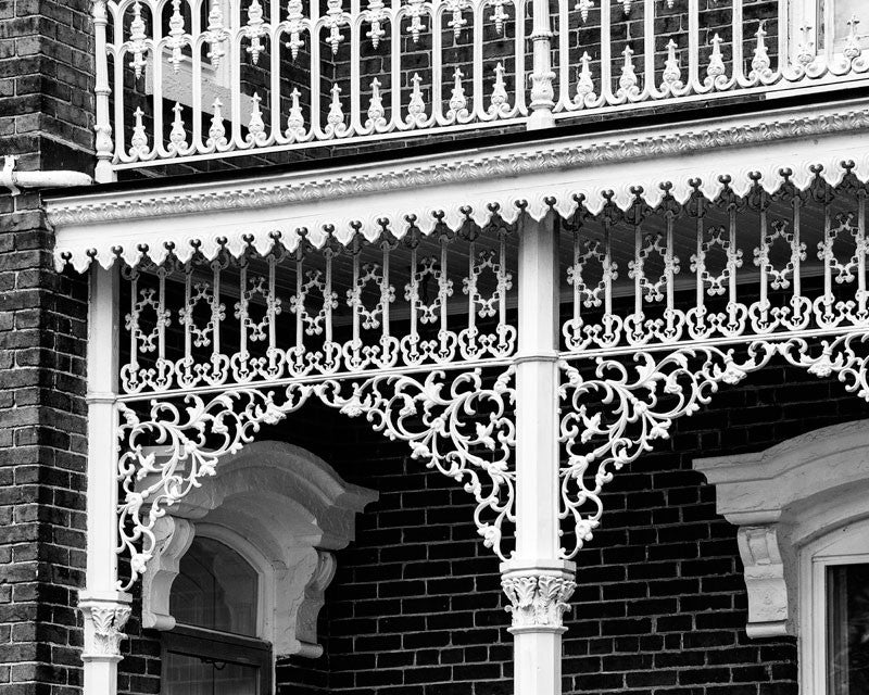 Black and white photograph of ornate, white lacy cast iron on the porch of a big Victorian house in the south. The ironwork is so intricate, it resembles like a white veil.