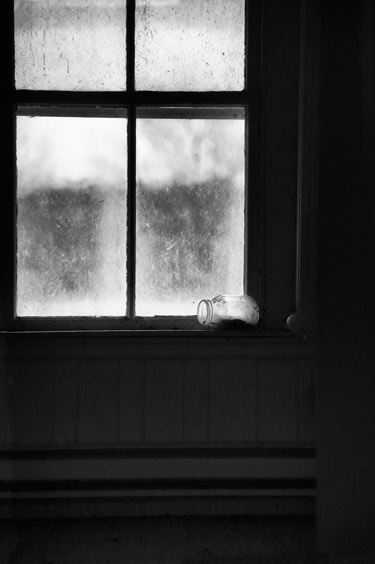 Black and white photograph of the dark interior of an abandoned old house, with frosty windows, and an overturned glass jar on the window sill, photographed as it was found.