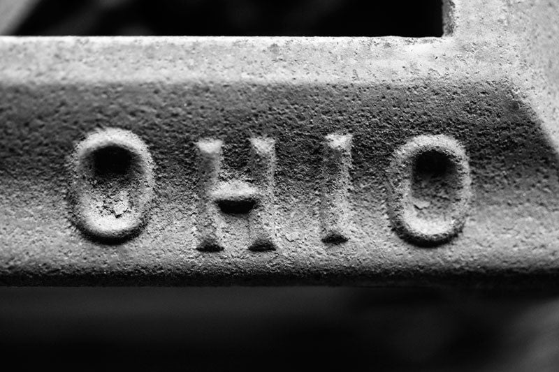 "Black and white photograph of the word ""Ohio"" stamped into the metal of a rusty antique piece of farm equipment."