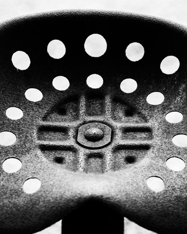 Black and white detail photograph of a rusty tractor seat on an antique tractor, cropped close to reveal details, textures, and the rivet in the center.