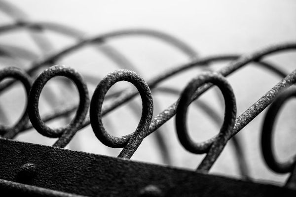 Black and white abstract photograph of rusty metal loops on an antique piece of farm equipment.