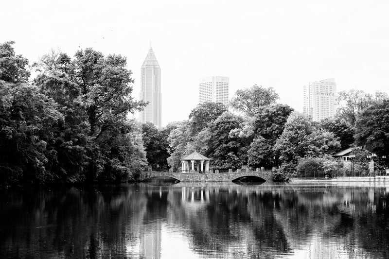 Black and white photograph of the Midtown Atlanta skyline, and the Piedmont Park gazebo reflecting into Lake Clara Meer in early morning light.