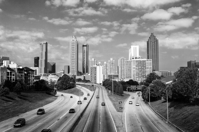 "Black and white photograph of the downtown Atlanta skyline as seen from the Jackson Street Bridge. Not only is this a perfect and popular spot to photograph the skyline, it's recognizable as the viewpoint used on one of the posters to promote the TV series ""The Walking Dead."""