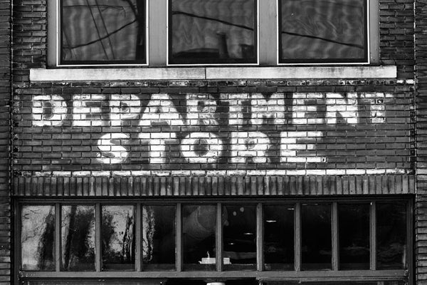 "Black and white photograph of a vintage painted ""Department Store"" sign on the red bricks of an old building in the same Atlanta neighborhood as the Martin Luther King, Jr. birthplace and his former church. Perhaps Dr. King even shopped in this store"
