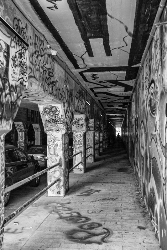 Black and white photograph of the notorious Krog Street Tunnel in the Cabbagetown neighborhood of Atlanta. The tunnel, under a bridge built in 1913, has been covered end-to-end with graffiti and street art.  This photograph is not available for commercial licensing.