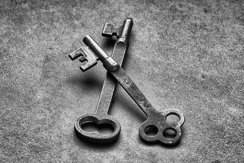 Black and white photograph of two antique keys found in Charleston, South Carolina. The top key is stamped with the date 1877.