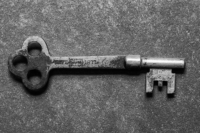 Black and white photograph of an antique door key stamped with the date 1877, found in Charleston, South Carolina.