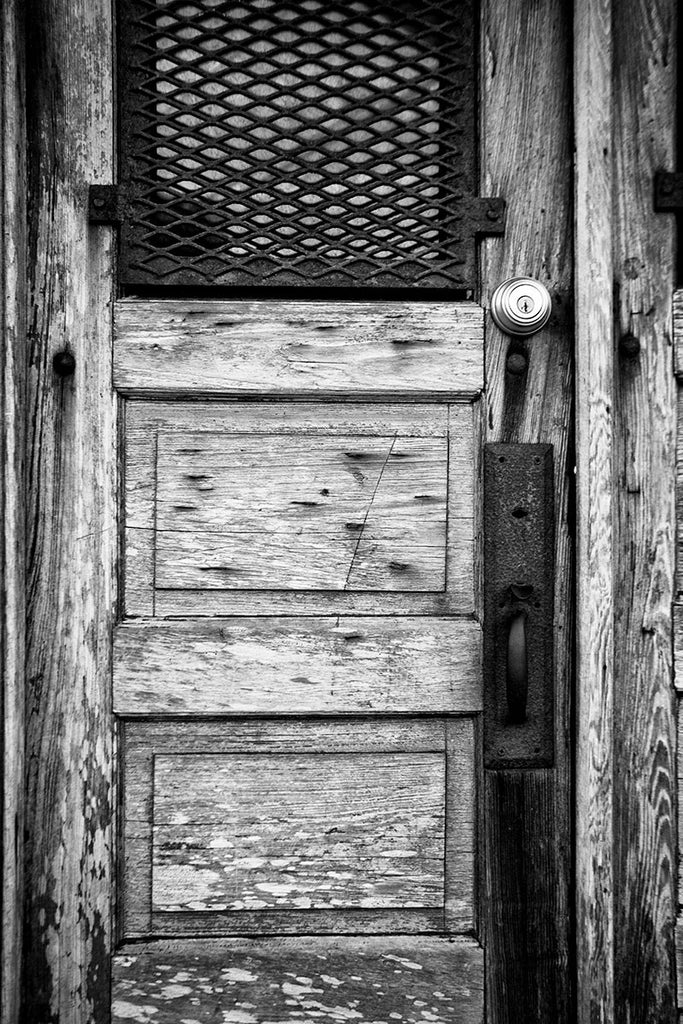 Black and white photograph of an rustic, weathered wooden door on the old drugstore in St. Augustine, Florida. The old Speissegger Drugstore in St. Augustine's old town was built as part of an upscale Victorian development in 1886 and operated as a drugstore / pharmacy until the 1960s. It's the last remaining structure from that development.