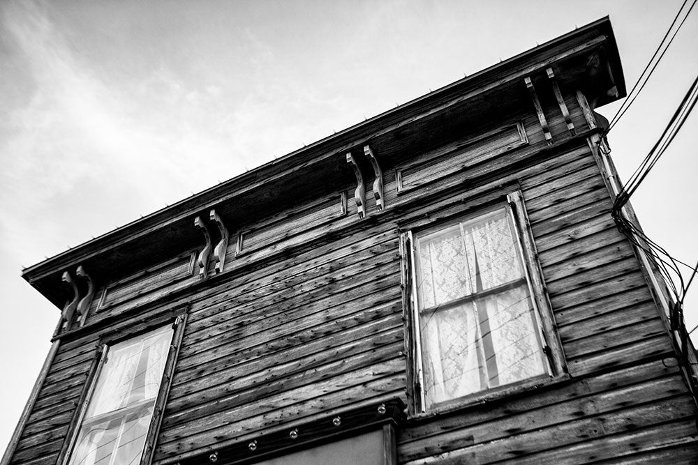Black and white photograph of the Italianate roofline of the weathered wooden 1880s-era drugstore in St. Augustine, Florida. The old Speissegger Drugstore in St. Augustine's old town was built as part of an upscale Victorian development in 1886 and operated as a drugstore / pharmacy until the 1960s. It's the last remaining structure from that development.