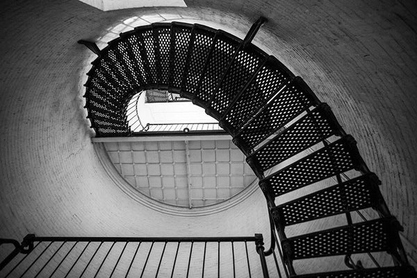 Black and white photograph of the metal stairs spiraling upwards inside the St. Augustine Lighthouse in St. Augustine, Florida. The current lighthouse stands at the north end of Anastasia Island and was built in 1874.