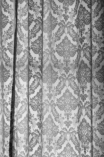 Black and white photograph of lace curtains in the old lighthouse keeper's residence at the St. Augustine Lighthouse in Florida.
