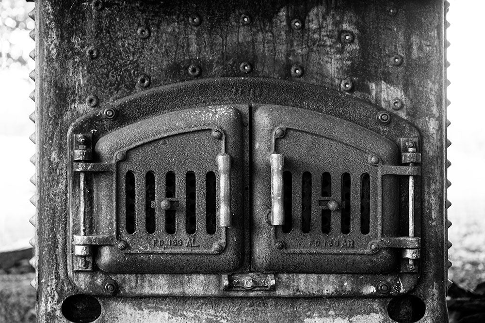 Black and white photograph of the grimy iron doors of an antique furnace.
