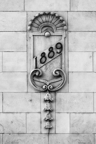 "Black and white photograph of an architectural detail featuring the date ""1889"" embellished across a crest, on the old Nashville Trust Building (now the Hotel Indigo). The crest features a scalloped clam shell motif of waves above the top edge, and flowers in a row along the bottom."