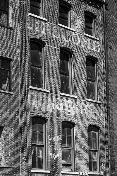 Black and white photograph of fading painted signs and ads on Nashville's old waterfront. At bottom left can be seen the turn-of-the-century Syracuse Plows ad.