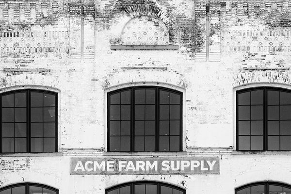 Black and white photograph of  the old Acme Farm Supply building on lower Broadway in downtown Nashville, Tennessee.