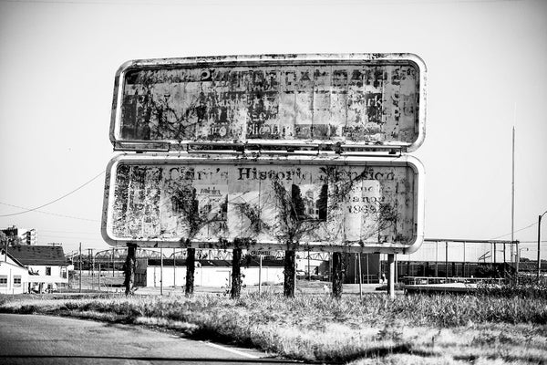 Black and white photograph of fading and peeling billboard signs that once welcomed visitors to the city of Cairo, Illinois, which itself is faded and peeling.