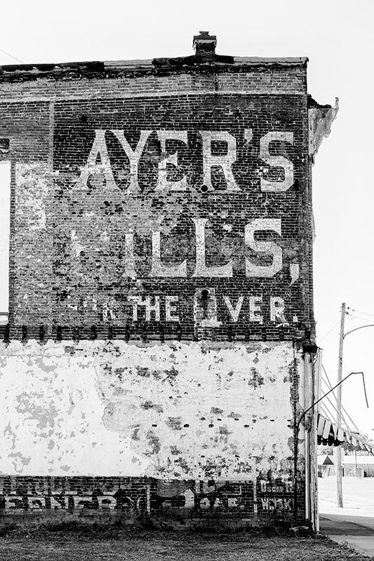 "Black and white photograph of a historic hand-painted wall ad for ""Ayer's Pills for the Liver,"" probably dating to about 1900, on an old riverfront building in Cairo, Illinois."