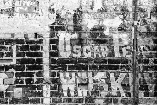 Black and white photograph of an old painted wall ad for Oscar Pepper Whiskey on the side of an old building in the city of Cairo, Illinois. Oscar Pepper established his whiskey brand in 1838, with roots as far back as 1800. The brand went on to become Woodford Reserve, still in production in Kentucky.