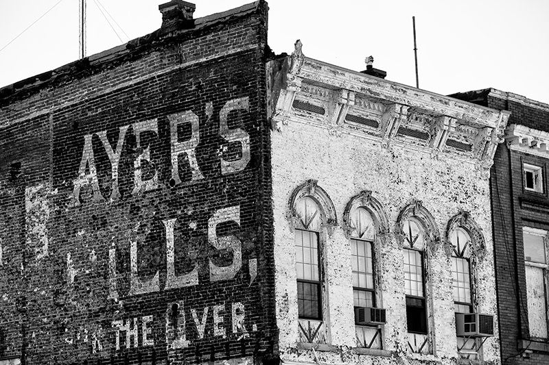 "Black and white photograph of a peeling painted wall sign for ""Ayer's Pills for the Liver,"" probably dating to about 1900, on an old riverfront building in Cairo, Illinois."