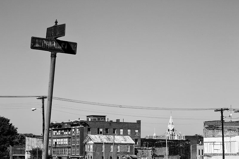 Black and white photograph of mostly abandoned Cairo, Illinois, with a rusty street sign in the foreground. Most of the buildings visible in this photograph are unoccupied and left to slowly decay.
