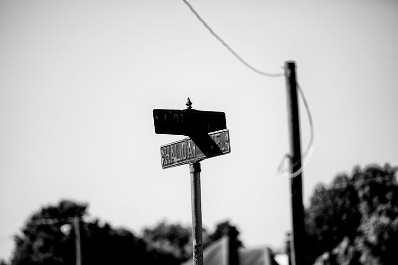 Black and white photograph of a rusty street sign for Haliday Ave in the city of Cairo, Illinois.