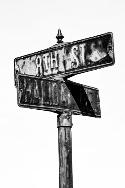 Black and white close-up photograph of a rusty street sign on Haliday Ave at 8th Street in the city of Cairo, Illinois.