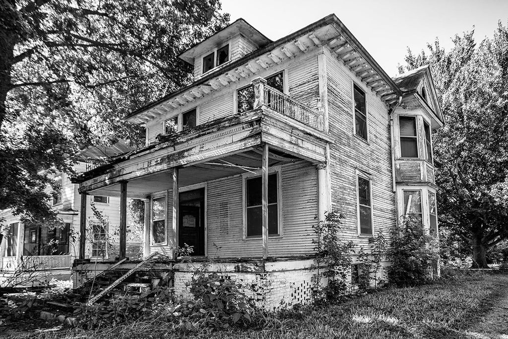 Black and white photograph of large, white house with peeling paint and broken woodwork, that has been abandoned and left standing wide open in a neighborhood.